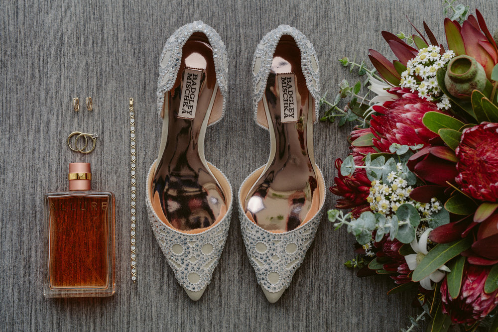 Flatlay of wedding shoes, bridal bouquet and perfume taken at The Shangri-La Sydney