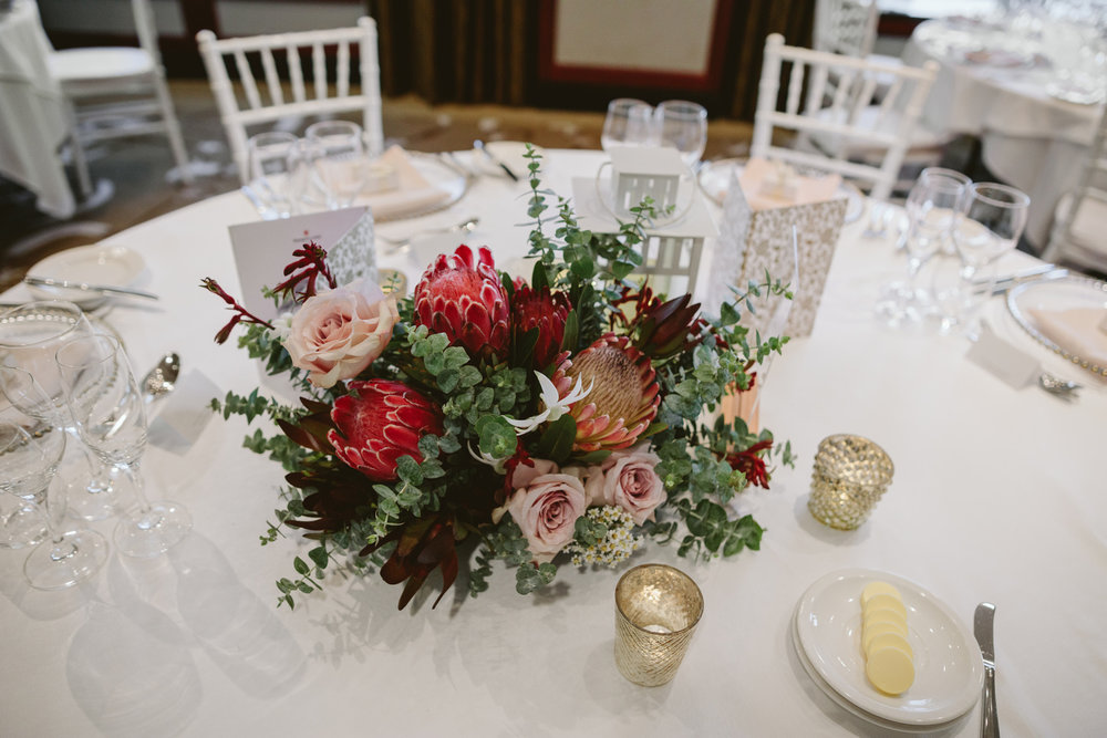Wedding flowers and centrepieces. Australian natives and pink roses with acrylic table numbers, gold candles and fairy lights