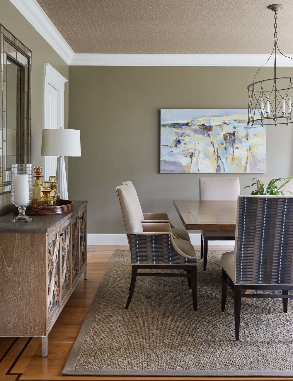 Deep rich mushroom colored walls are a backdrop to the Dining Room's transitional furnishings that feel collected.