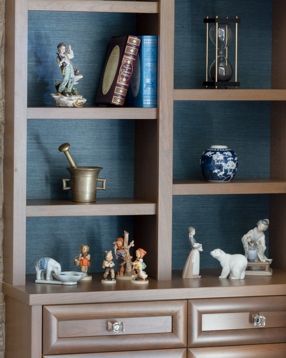 Deep blue textured grass cloth accents bookshelves with cherished figurine collections.