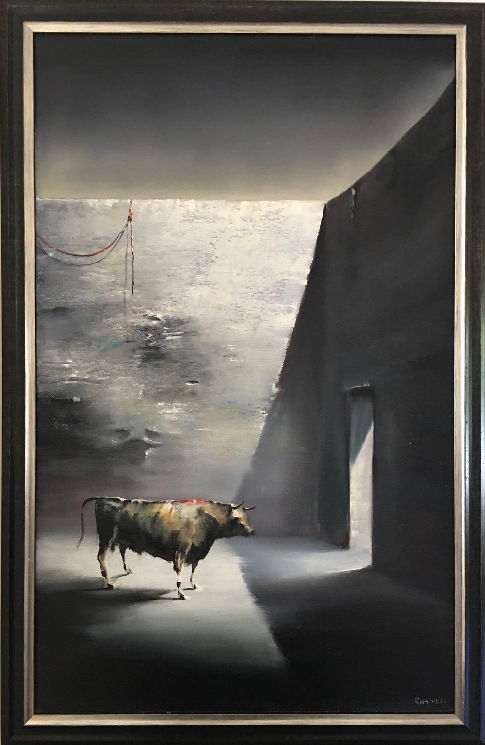 A black frame accented by a silver edge focuses the eye on the light surrounding the bull.