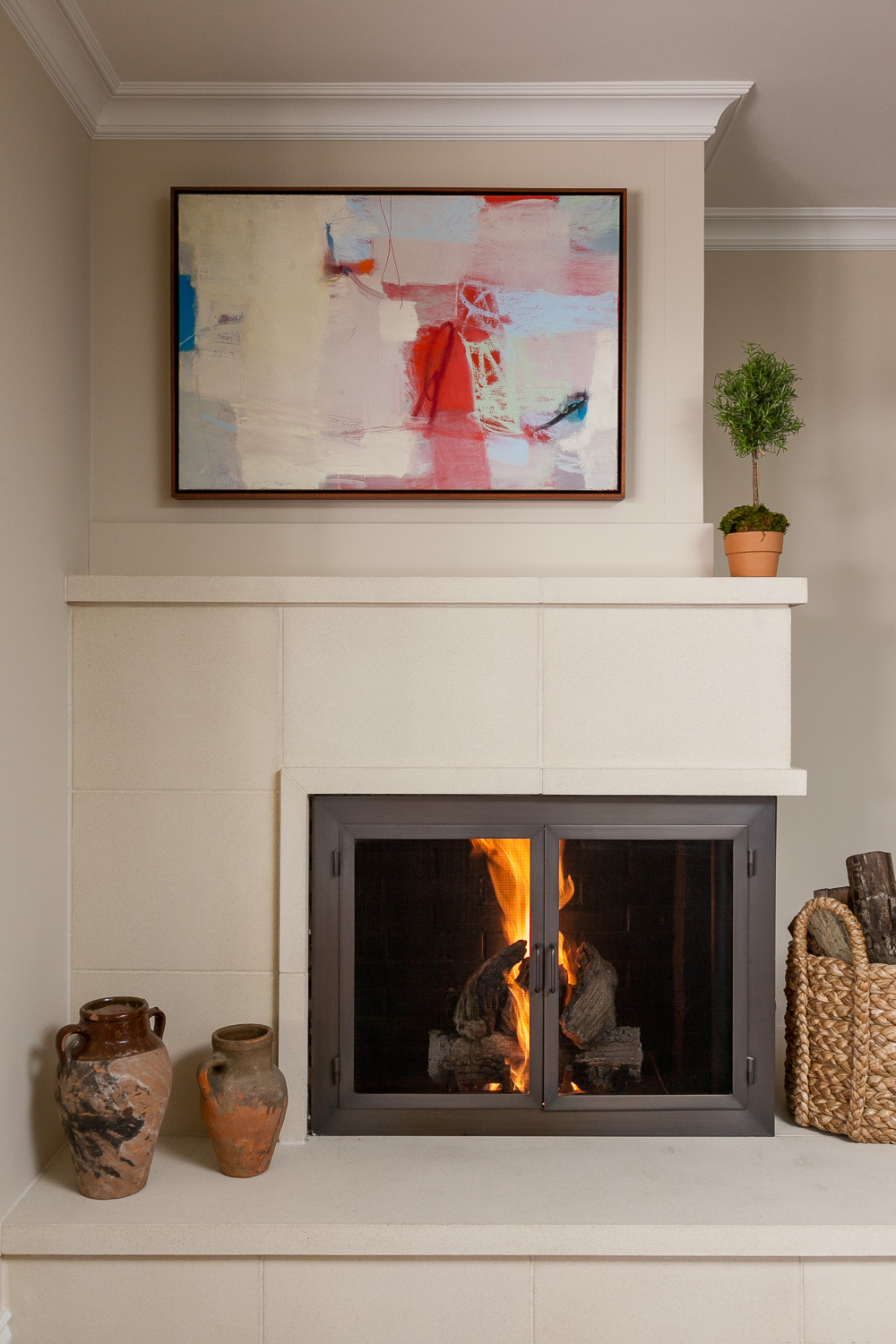 The play of neutrals with a pop of color by artist was a perfect fit over the fireplace in the client's family room.