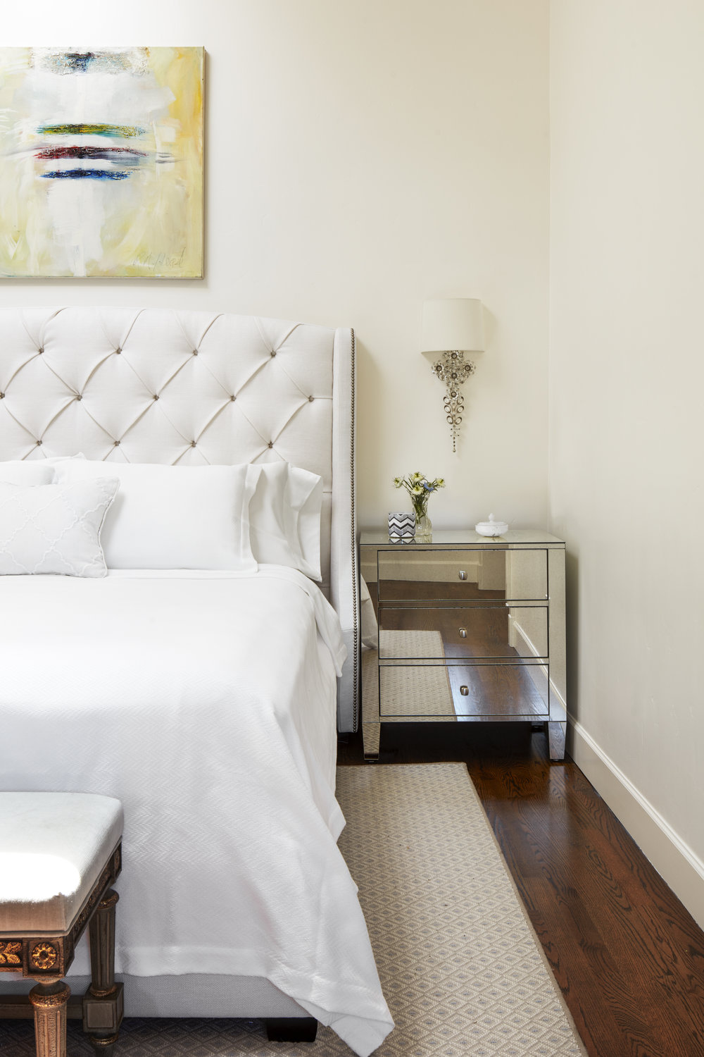 A beloved piece of the client hangs above the headboard in an all white room.