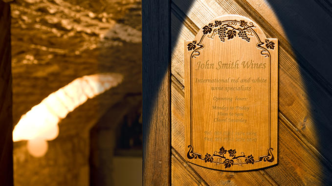 Directional and functional signage: engraved and sculpted wooden plaque for visitor information