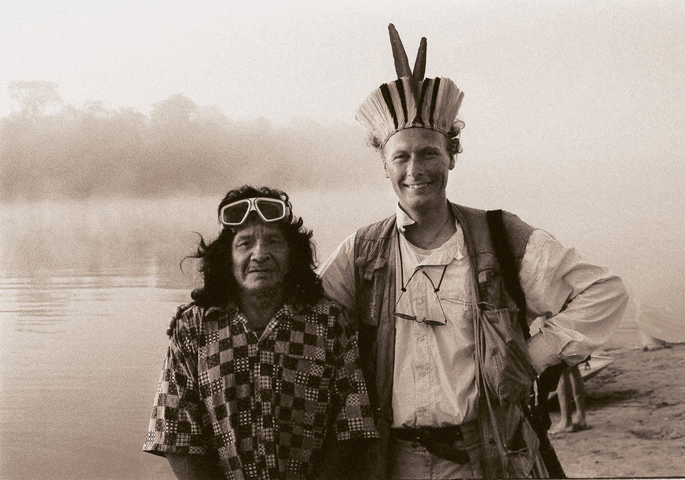 Suya River, Xingu Province, Amazonia, Brazil : Chief of the Suya tribe and Per Fronth bids farewell one misty morning along the Suya river in August 1996. But before the departure in to the small carved out wooden boats we exchanged gifts; underwater goggles for a beautiful headdress.