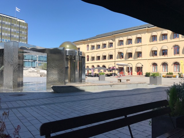 View of the fountain in the public square at the train station, from Baker Hansen Cafe, Drammen