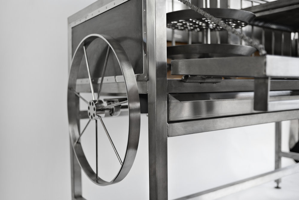 The hand operated carousel rotisserie works by manually rotating a wheel as small increments at a time. The wheel operates smoothly and with ease.