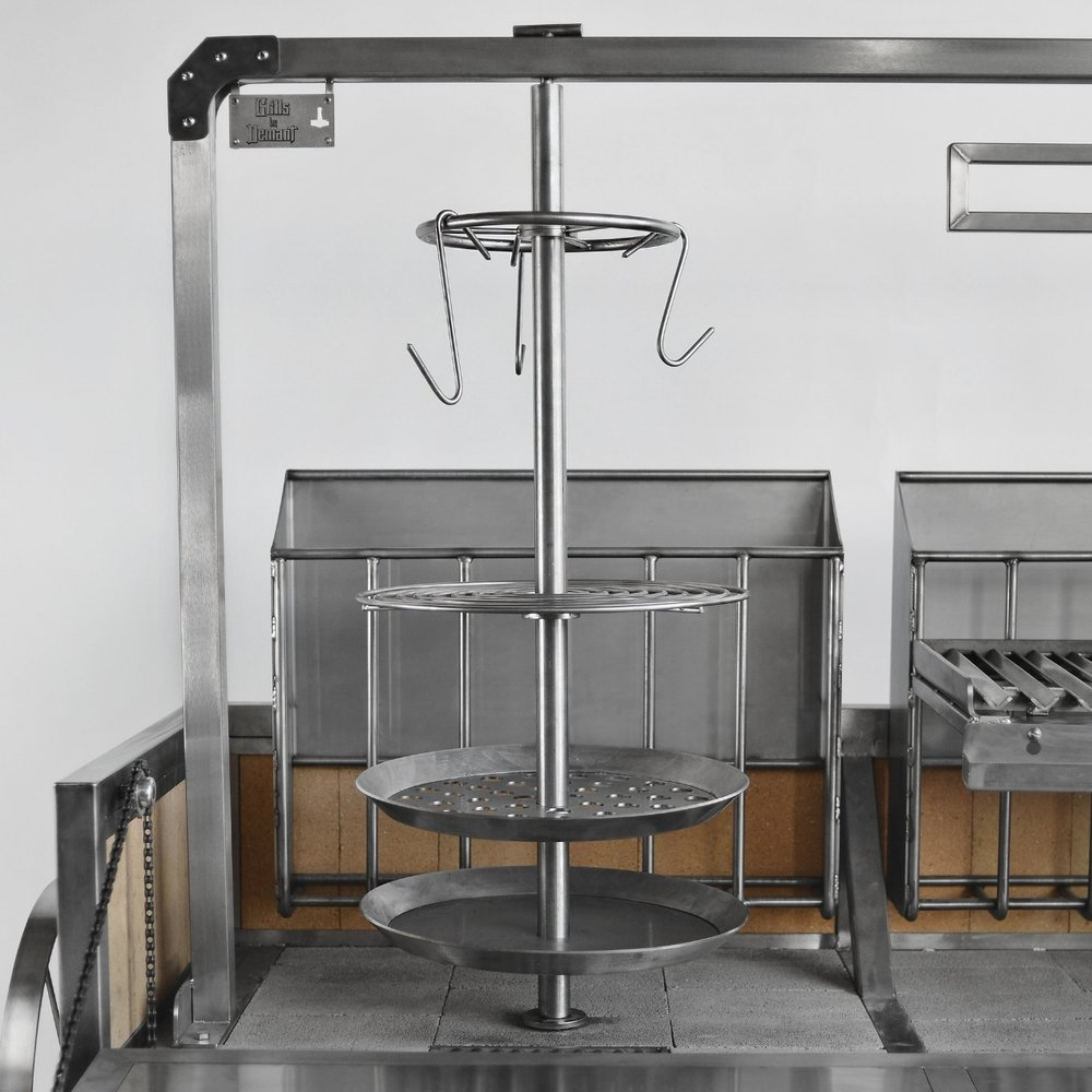 The carousel rotisserie is a different way of grilling by using the burn box as a heat source. Different grates can be adjusted to the desired height settings or can be removed and the spid utilized as a gyro. The intended heat source is the burn box in the back, which makes a wall of heat. The bottom tray can among others be used as a drip tray to collect juices, as a frying pan or fill it up with coals as an alternative to the burn box.  The thought behind the vertical system is, that fat and juices can drip down from the top and help flavor and baste the layers below.