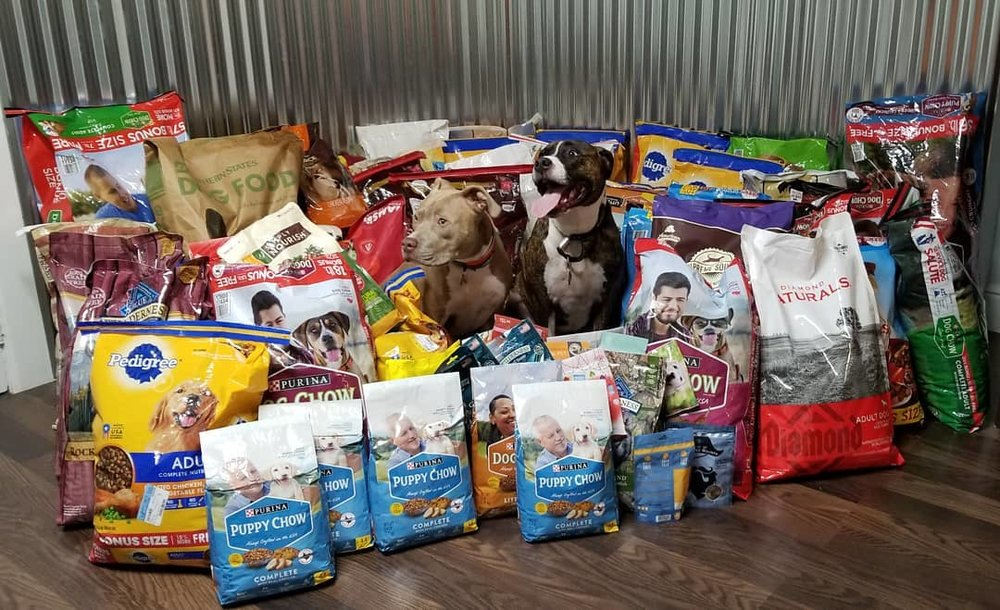This is a photo of the 856lbs of dog food we collected at this year's event with our two Pitbulls, Caesar (dark brindle) & Alpha (light brown). They are so glad we all help their doggie friends have full bellies!