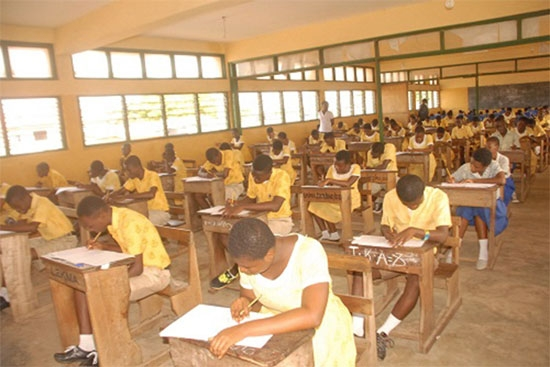 Ghanaian JSS students completing an examination