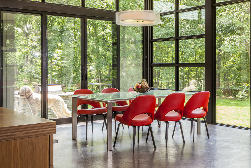Modern dining area with glass windows and six red chairs
