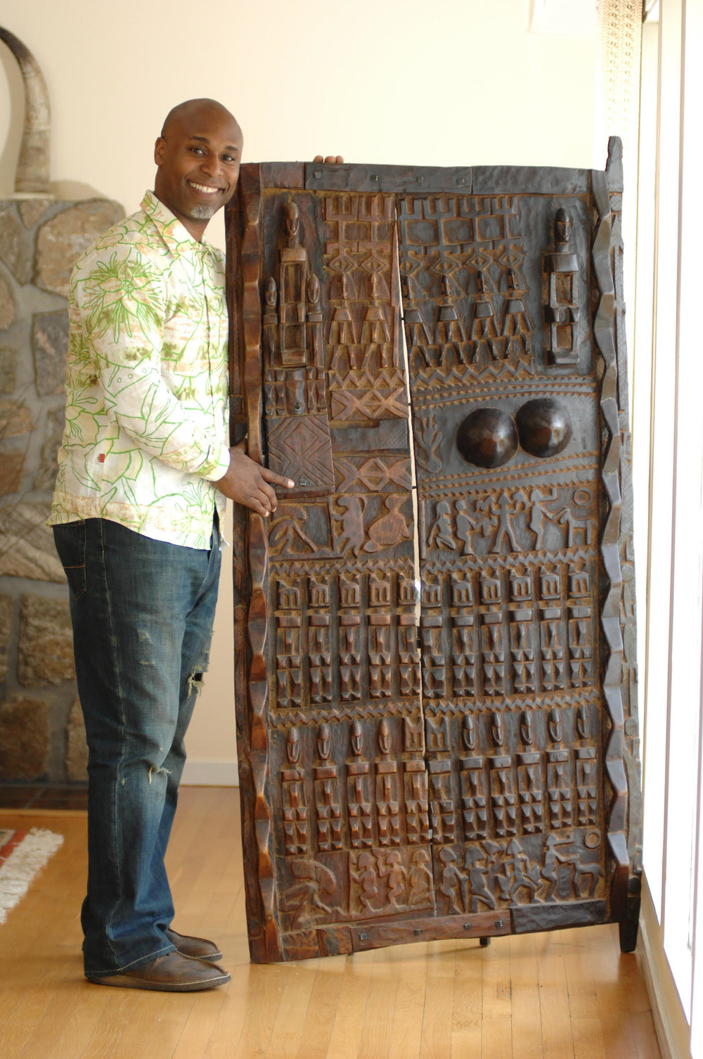 Everick Brown holding wooden sculptures