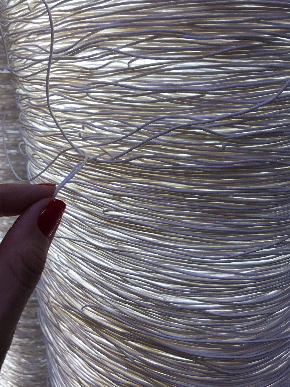 Touching the Japanese cord used for one of the sculptural lighting design by Arturo Alvarez.