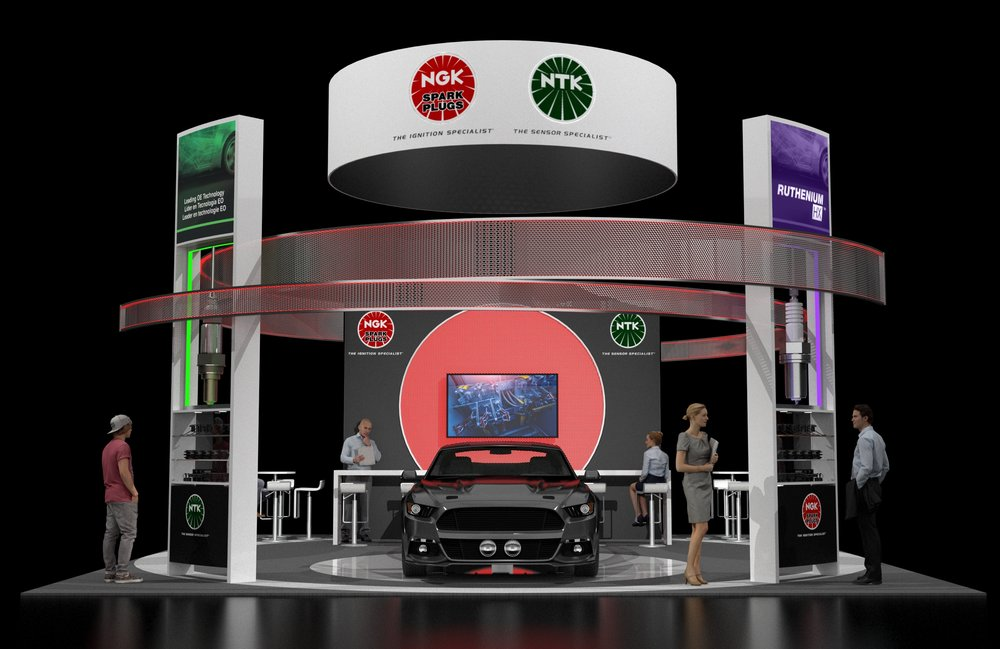 Hanging Circular ID (re-purposed from existing 2017 AAPEX header) provides a strong branding opportunity. The right and left towers/product displays enhanced with LED lighting, graphics and oversized sculptural spark plugs/oxygen sensors to draw attention to the booth. The challenge was to create a cohesive look using red, green and purple colors per design brief.
