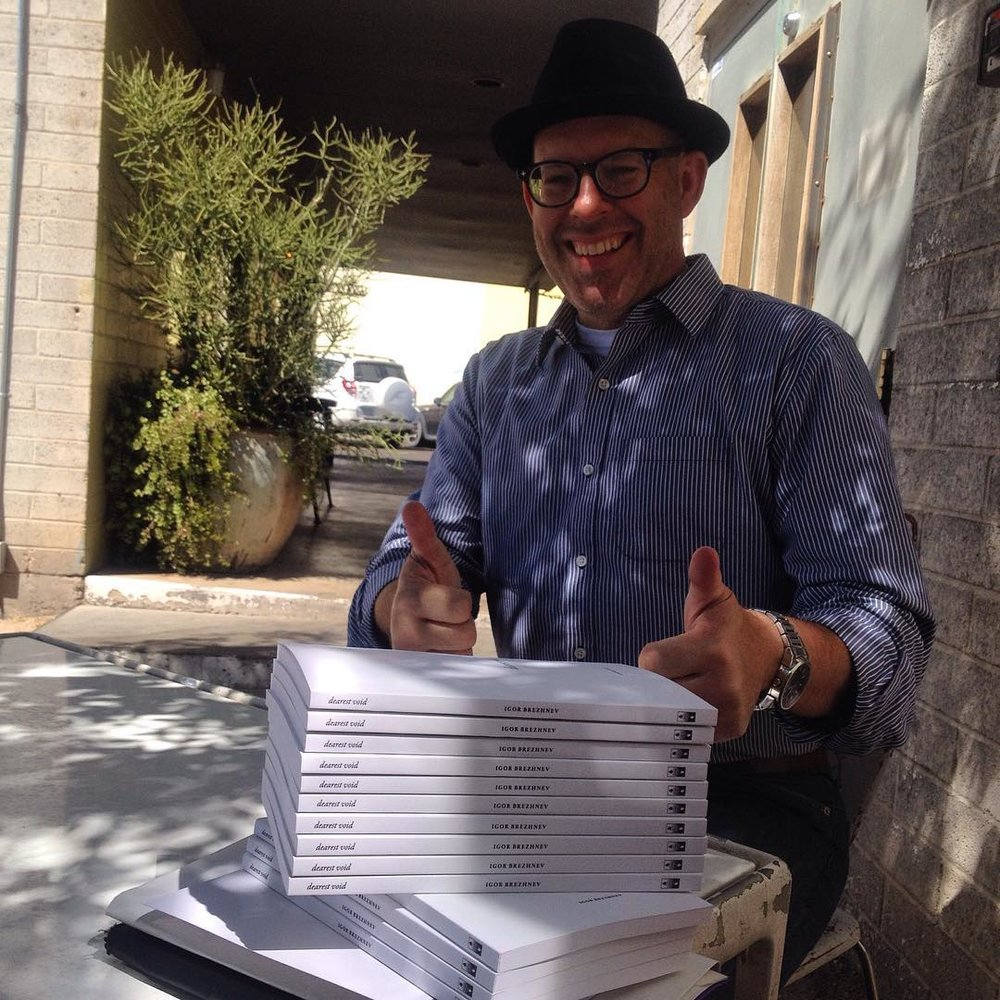 The publisher Joey Robert Parks with the stack of copies of dearest void.