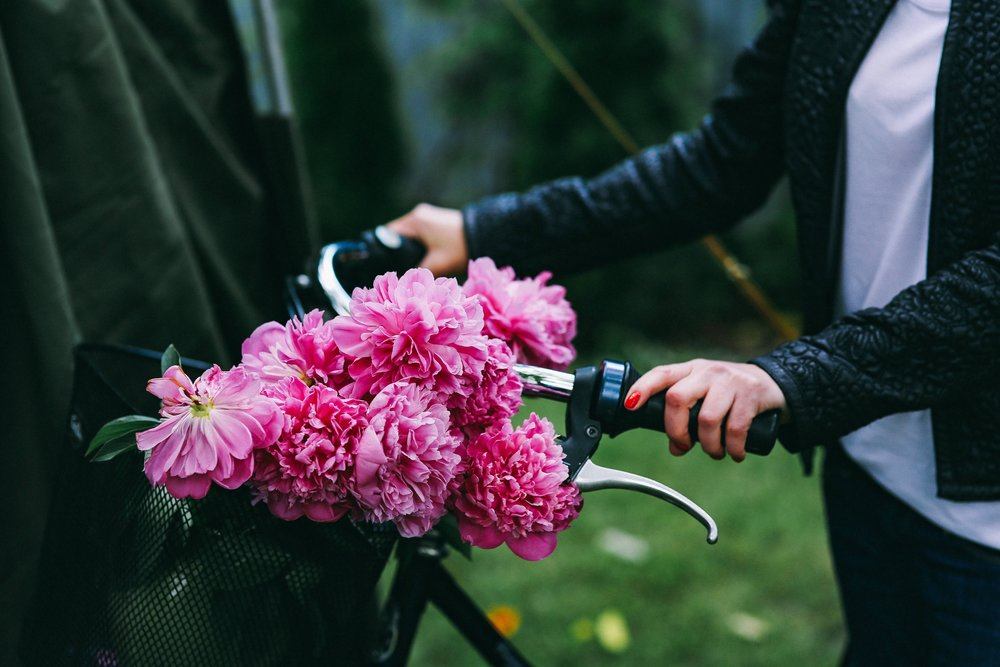 kaboompics_Woman holding a bicycle with beautiful pink flowers in the basket (1).jpg