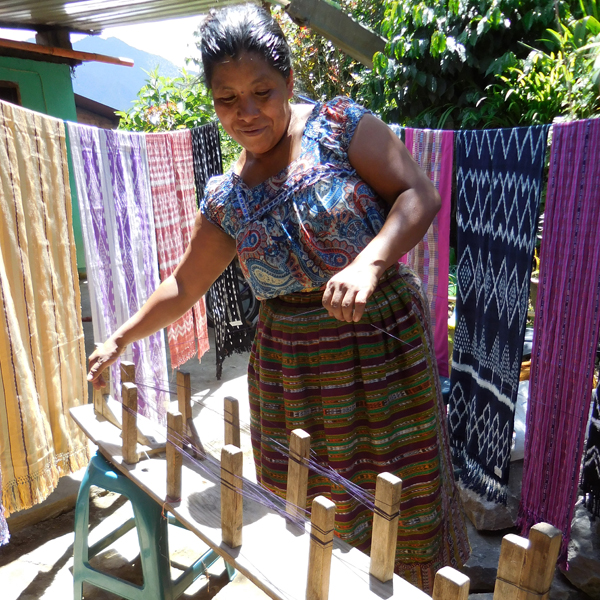 A woman starting the weaving process.