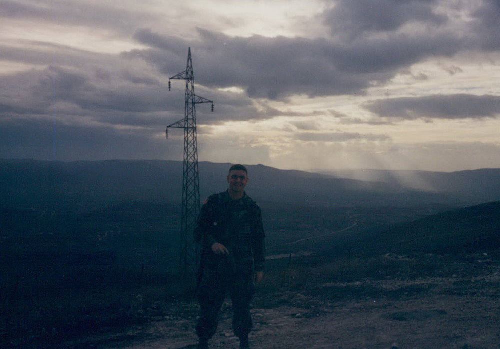 Here I am just outside Film City, Kosovo, guarding a communications depot. We patrolled the perimeter in 12-hour shifts. We were on top of a high point that was shared with the British & Italians. They told us the entire eastern/northern portions of the hill were littered with land mines. There was melted armor and old, shelled buildings from Slobodan Milosevic's forces left over from bombings in the '90s.