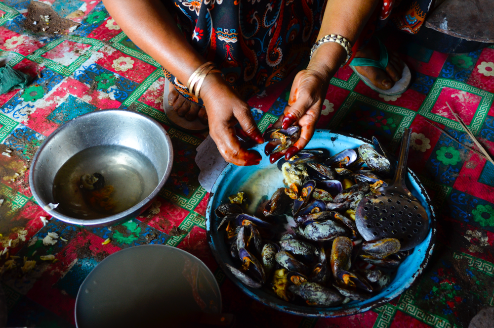 Detwah Lagoon, Socotra, Yemen, 25 May 2014. Sadiya prepares mussels for lunch.