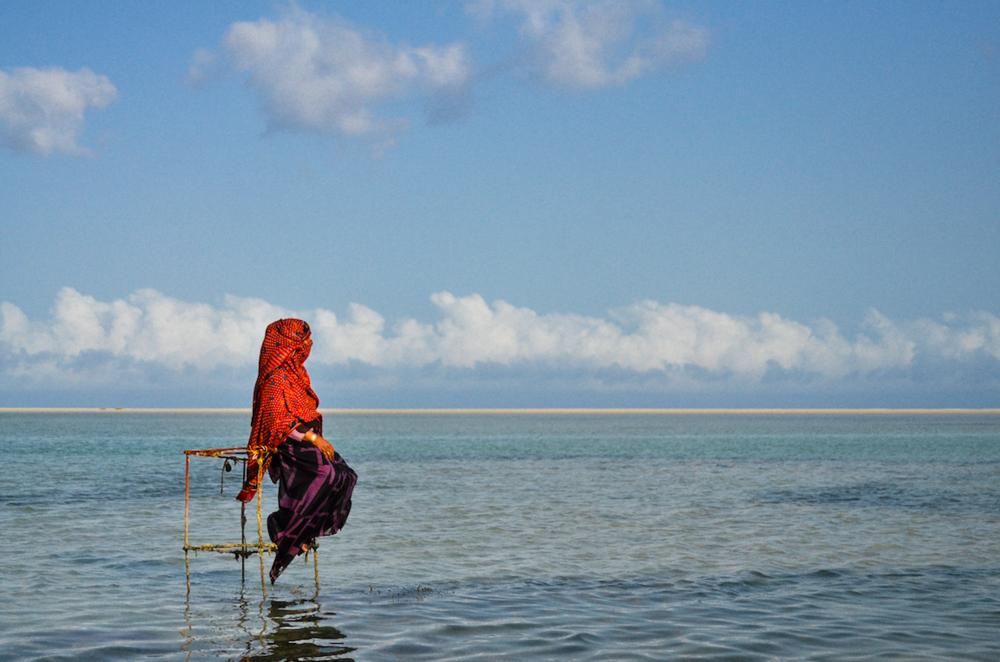 """ديطواح لاجون ، سقطرى - اليمن، التاسع عشر من مايو 2014. سعدية جالسة على قفص سمك معدني متآكل كانتْ تستعمله حين كانت تذهب لاصطياد الأسماك  هذه سلتي المعدنية التي استخدمتها لاصطياد الأسماك. لم يتبقَ منها"""" إلاالهيكل. بقي الهيكل ذكرى أيام مضت. أراد الصيادون أن يأخذوها خارج البحر، لكني منعتهم. على الأقل نستطيع الجلوس فوقها في البحر نفسه. غدت الآن معلما وعلامة في البحر؛ إذا وضعت شيئا تحتها فإنك تستطيع العثور عليه مجدداً. أكثر من ذلك تستطيع فيها أن تخبيء الصدف ثم تأخذها في وقت لاحق، وهذا أفضل من الضرب في عرض البحر والعودة خالي .""""الوفاض"""