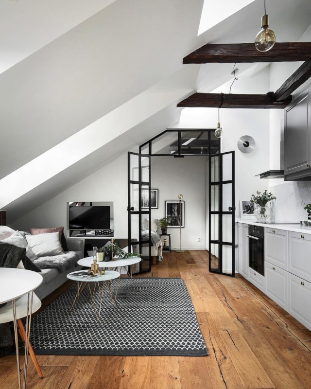 Warm wooden floors and stained exposed beams warms up this white minimalist attic space. Photo by @kronfoto