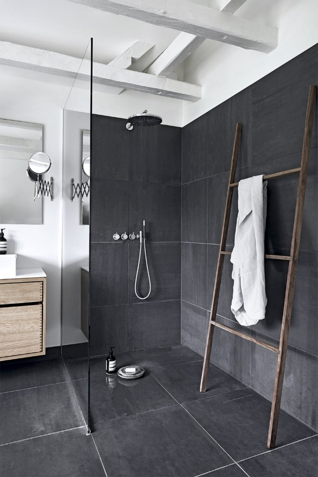 Using large tiles in a neutral colour, combined with white and wood creates a calm and spa-like feel to the bath. Separating the shower with a glass wall gives the illusion of a larger space, and allows light to filter in.