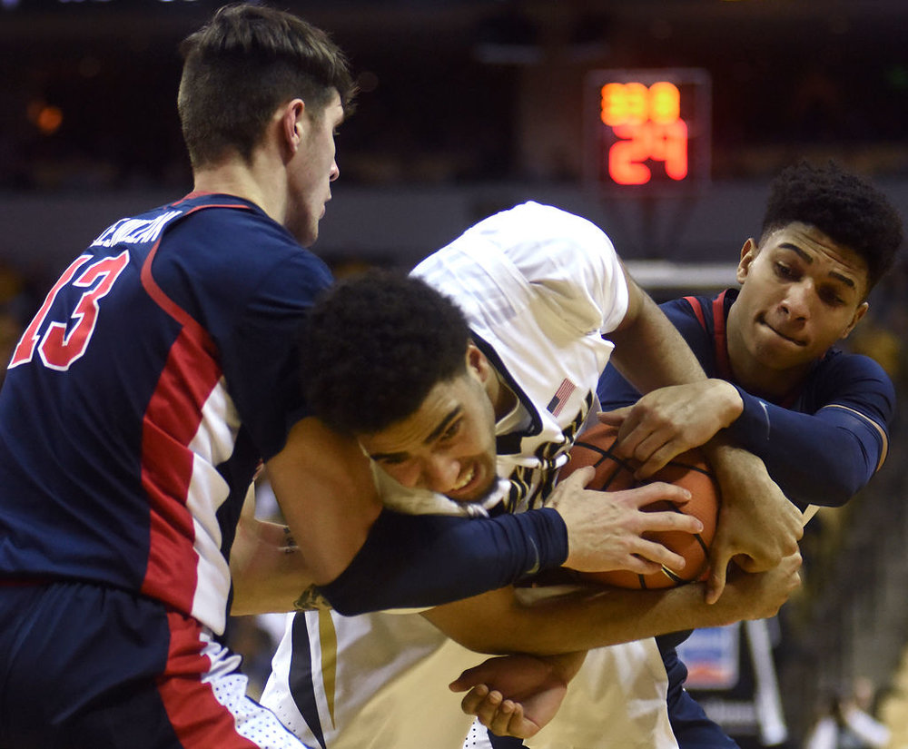 Missouri forward Jontay Porter, center, struggles to keep possession of the ball against Mississippi center Dominik Olejniczak, left, and guard Breein Tyree, right, during the first half of the Tigers' 90-87 overtime loss to Ole Miss on Tuesday at Mizzou Arena.