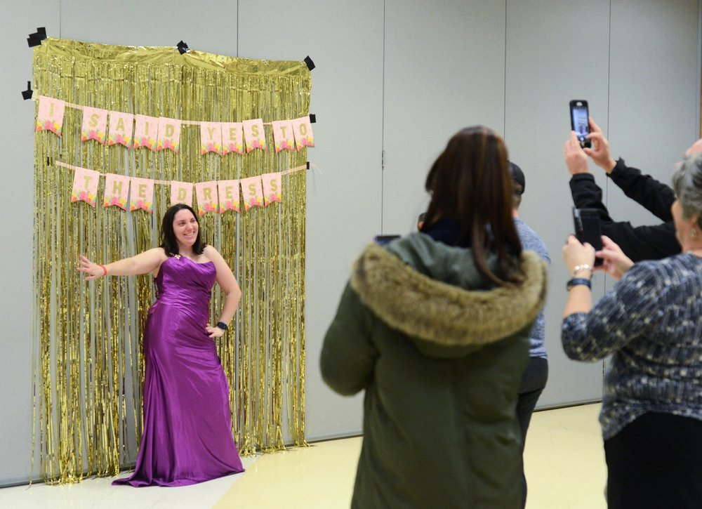 """Say Yes to the Dress"" participant Jessica Cain, left, poses in front of a backdrop for a handful of photographers on Wednesday, Jan. 17, 2018 at the Activity and Recreation Center in Columbia, Mo. Cain tried on several dresses before settling on a vibrant, purple dress. The goal of the ""Say Yes to the Dress"" event was to make those attending the Night to Shine prom in February feel beautiful and confident."