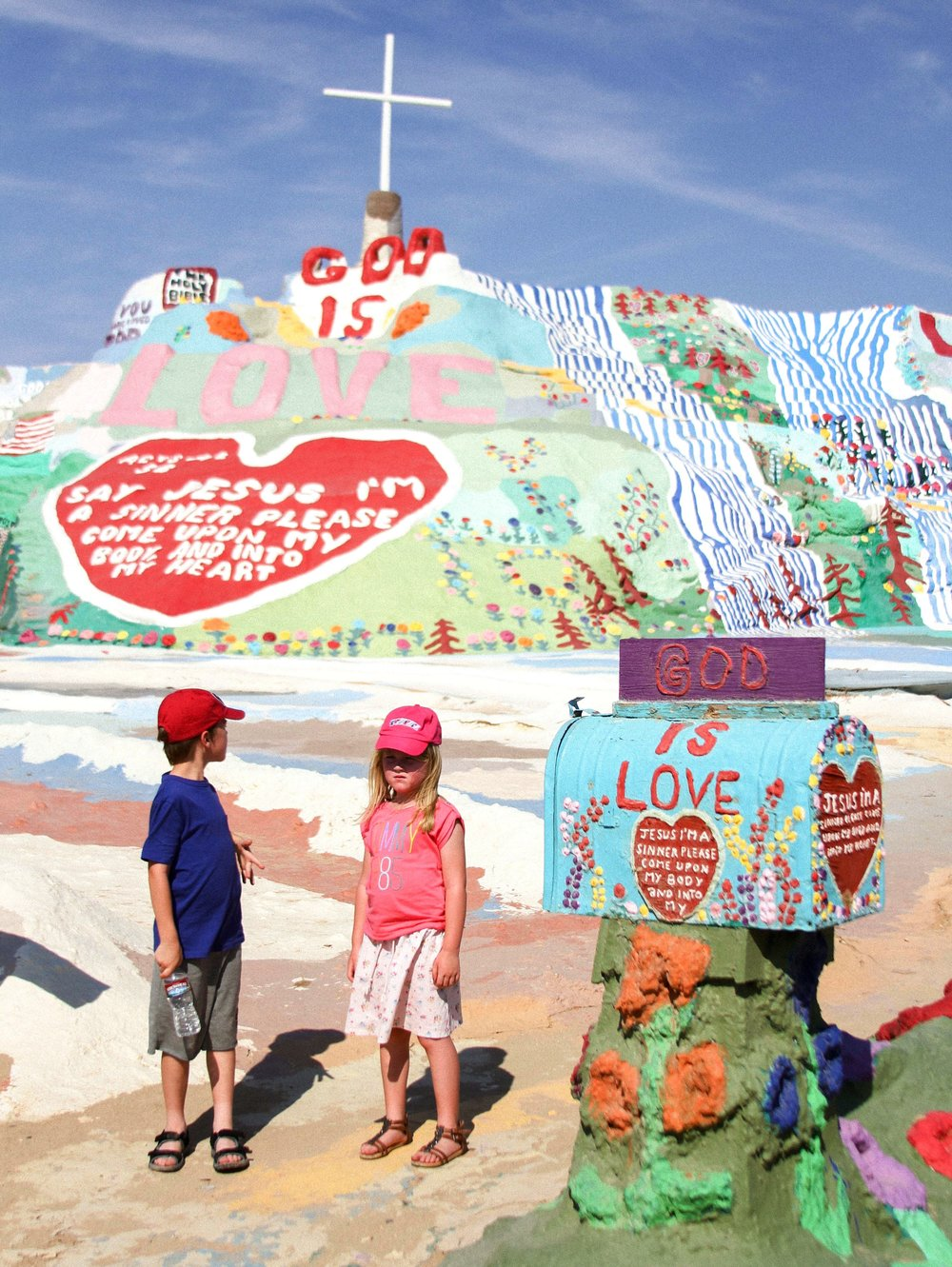 "Two children wait for their parents to take their picture on Tuesday, July 29, 2014, at Salvation Mountain in Niland, Ca. Salvation Mountain is a man-made mountain created by artist Leonard Knight and is based on the Christian term, ""Sinner's Prayer""."