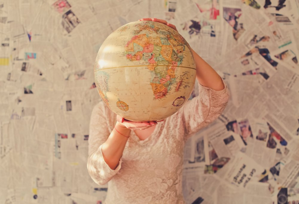 Vintage cream world globe being held up by lady. Background wall covered in newspapers.