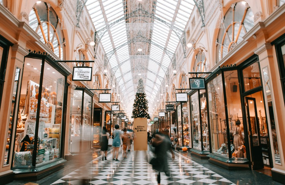 Melbourne, Australia victorian looking shopping boutique mall at Christmas with hanging white lights, black and white checkered floor. Christmas tree in middle with blurred images of customers walking past.
