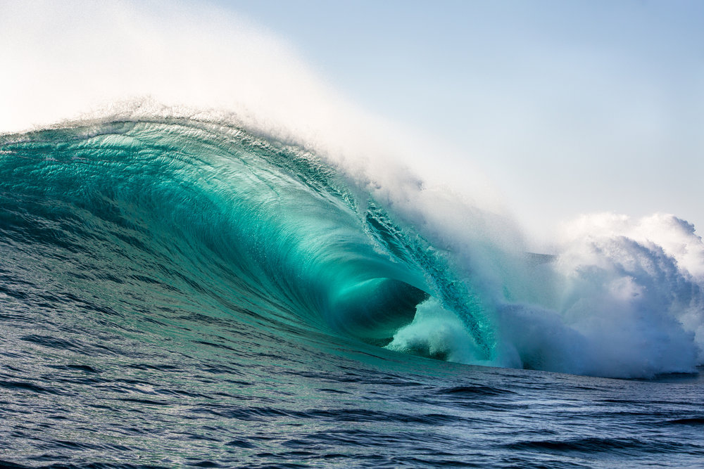 Giant turquoise wave crashing out at sea with large plume of white spray in background