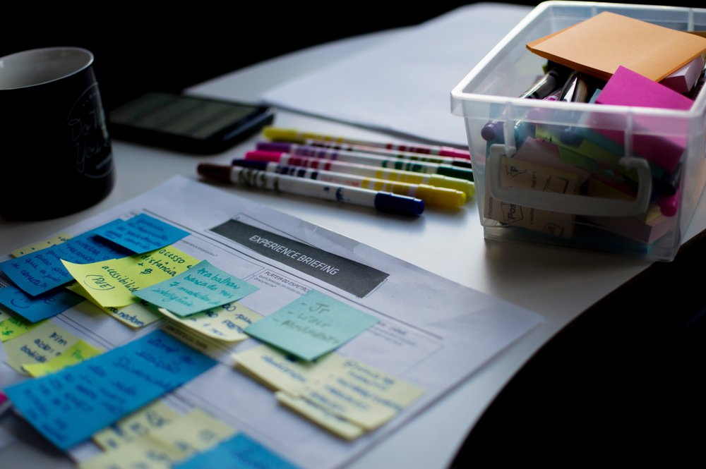 image from felipe frutado unsplash. Bright yellow and blue post it notes and crayons on white desk