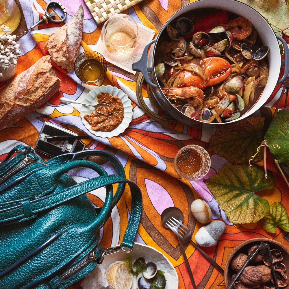 "MELINA HAMMER  ""I dreamt up a parade of colors and an over-the-top ""ladies picnic"" theme to go with the bag. Who doesn't bring a pot of goodies with them on a grand picnic?! Inspired by two dames who knew great style, I made a  delicious riff on Julia Child's bouillabaisse , added artifacts (and a tablecloth) from my grandmother, and accented the scene with foraged and found treasures from my collections. Absolute play."""