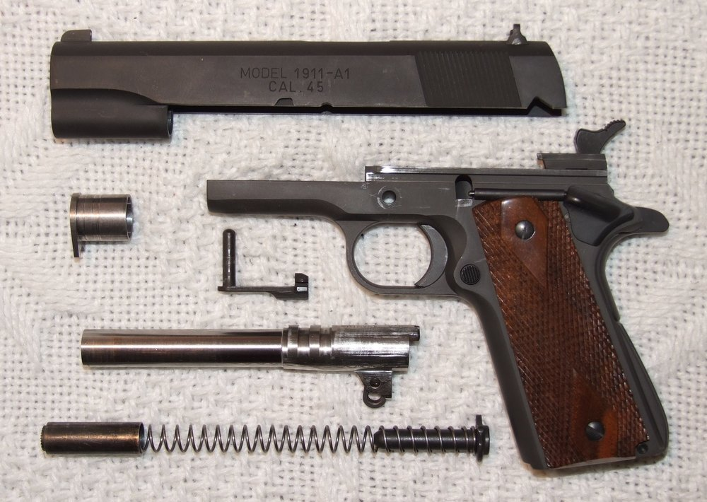 a M1911-style pistol broken down for routine maintenance.