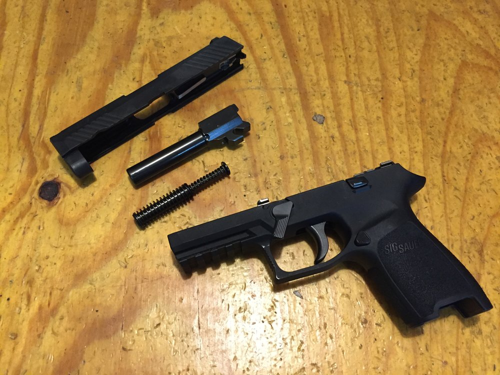 A Sig P320 broken down for routine maintenance.