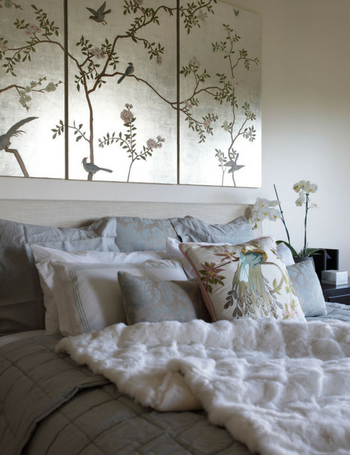 Bedroom detail - Muted gold artwork panels specially commissioned by artist Alexandra Heyes combine with the luxurious textures of a white fur throw and embroidered cushions to create this delicious bedroom haven.