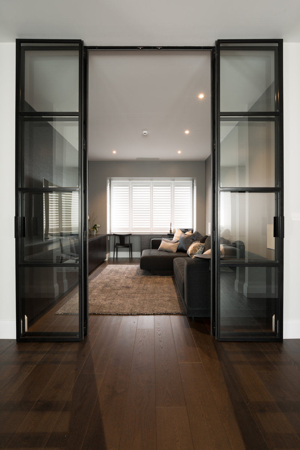 - Contemporary black steel doors lead to the Media room painted in charcoal greys and black stained custom designed joinery.