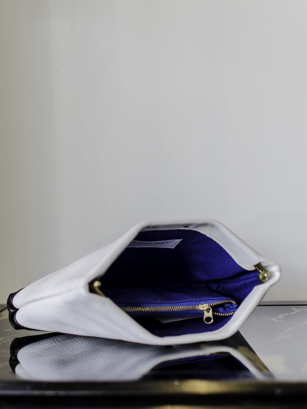 Open Habit Blackand White Clutch - This clutch is all business until you pop it open and discover the electrifying blue inside! It would fit my sister so well, since she's sooo professional now but we all know she's a party waiting to explode!