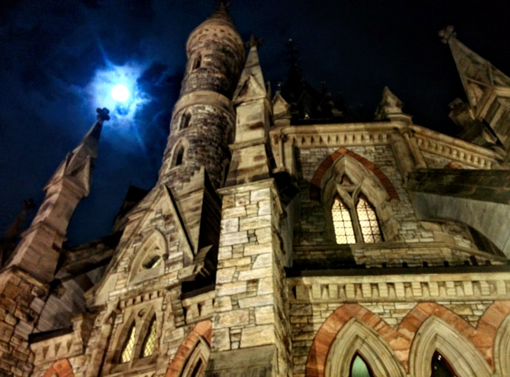 The castle-like facade of the library at Parliament nearly outshines the moody moon on an unseasonable warm Christmas Eve, 2015.