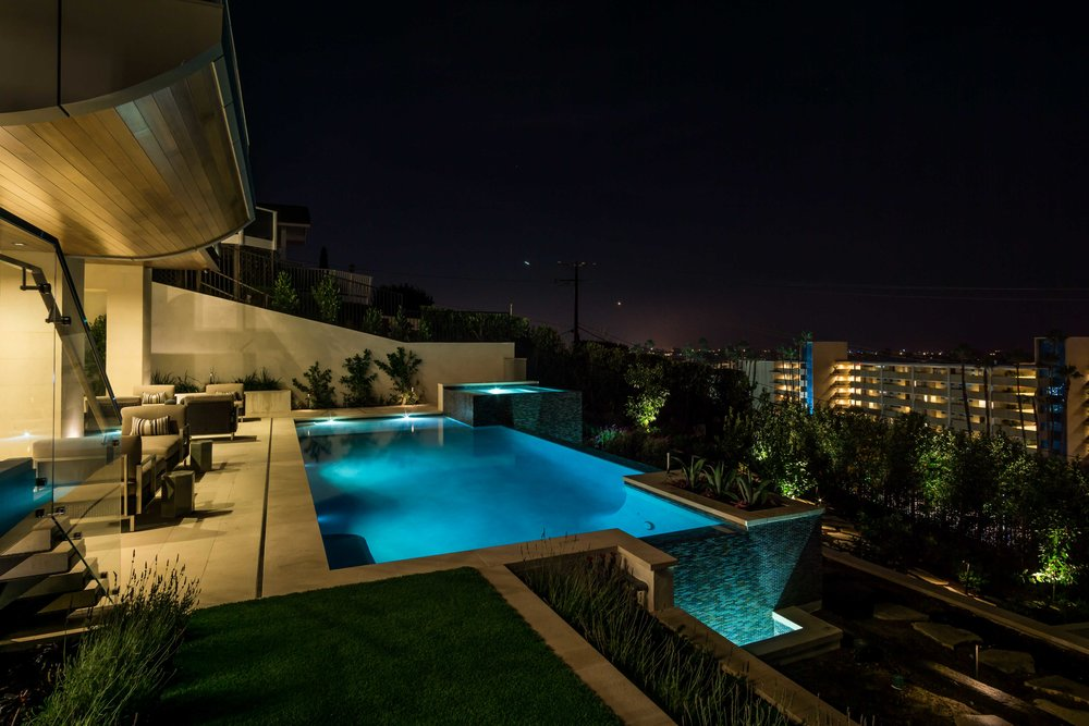 Wide-angle photograph modern luxury's infinity swimming poolIn Newport Beach overlooking PCH and Balboa Harbor