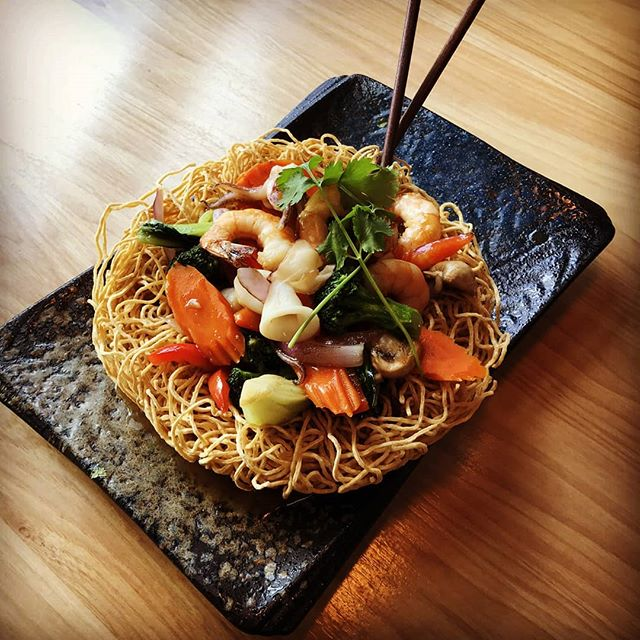 "Our current special is Tổ Chim, which means ""birds nest"" 🐦. This dish features a nest of crispy egg noodles with sautéed veggies, shrimp, calamari, and scallops. Dig in!!!"