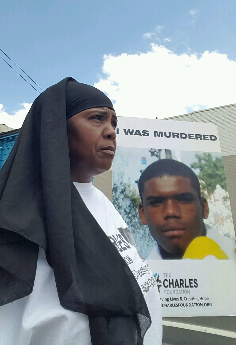 The Founder of The CHARLES Foundation, Movita Johnson-Harrell, with a poster of Charles Johnson