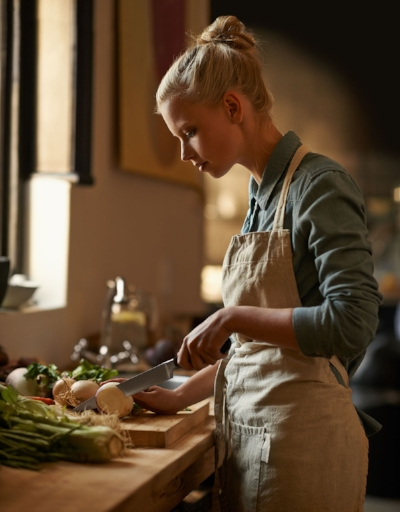 Easy Gluten-free Cooking is the home of Easy Delicious Gluten-free cookbooks blonde woman wearing apron slicing vegetables in kitchen