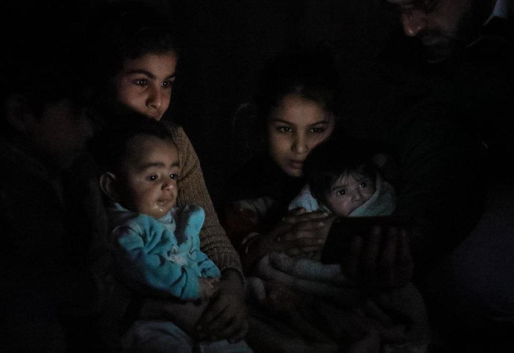 Eine Familie kauert im Dunkeln in ihrem Kellerunterstand in Ost-Ghouta, Syrien. Quelle: Abdullah Hammam/IRC