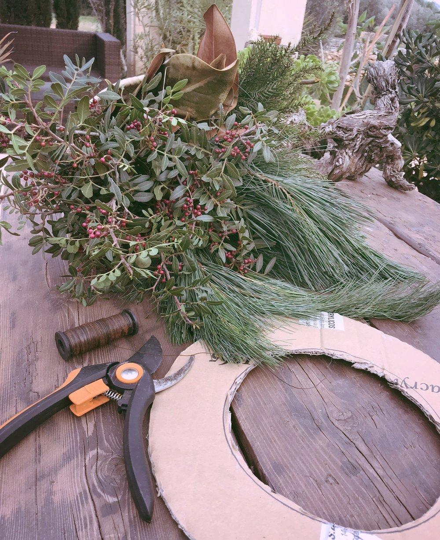 Pino, mata con bayas rojas, ramas de otras coníferas, alambre, tijeras de podar, y un aro, en este caso, como no tenia nada mas, use cartón.
