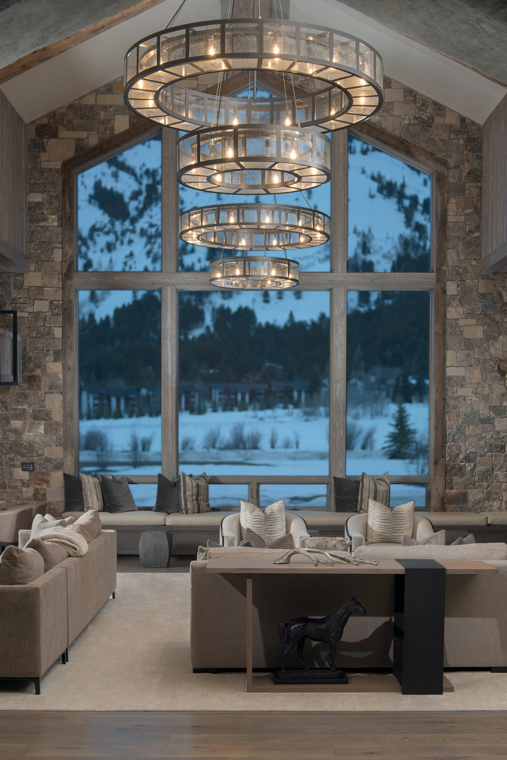 Above, a pair of two-tier Nested Ring chandeliers cleverly draw the eye up toward a magnificent view of the Tetons. By KAM Designs.