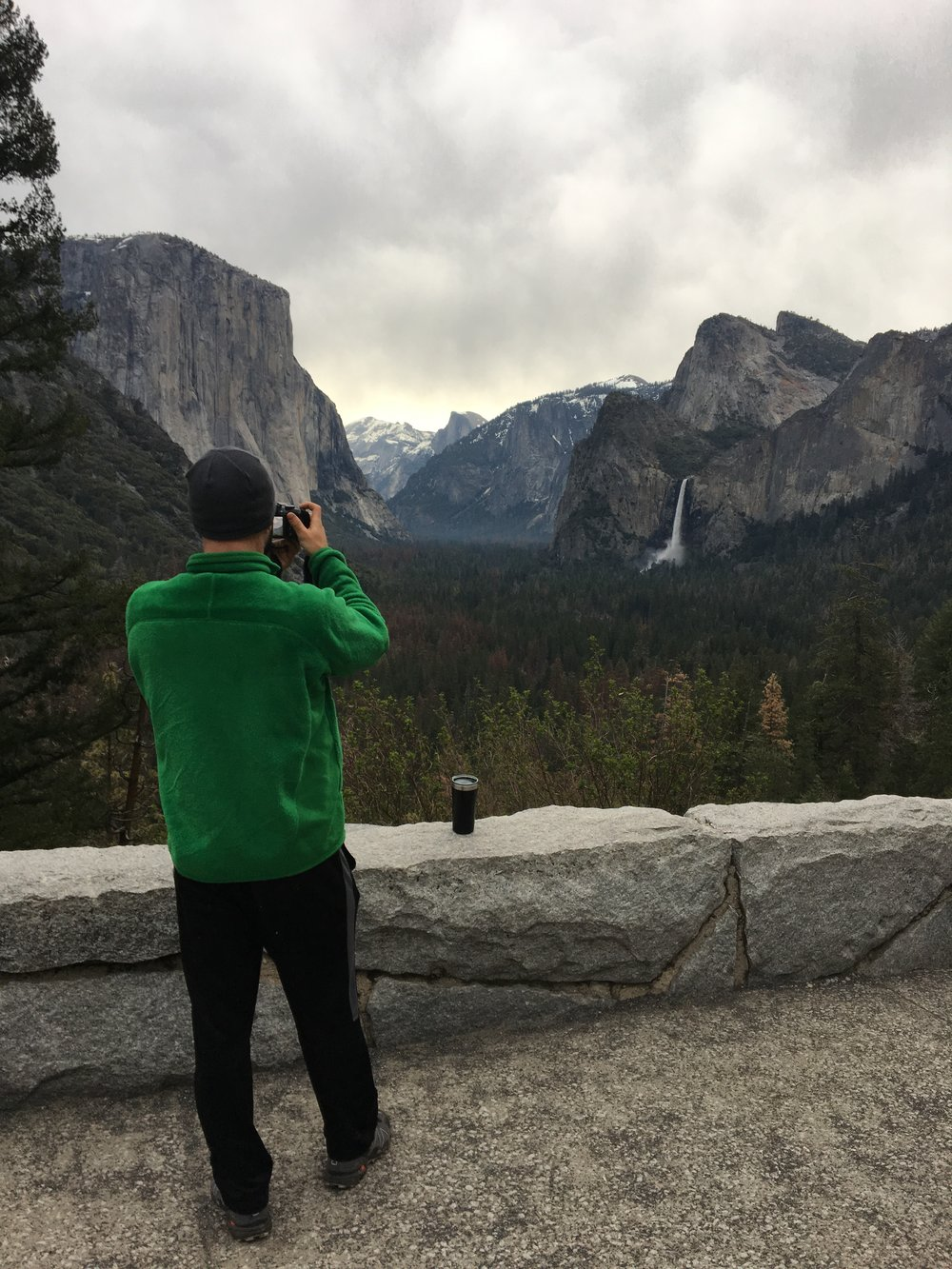"My handsome photographer in his ugly green jacket (which I have dubbed ""The Grinch"") photographing Tunnel View"