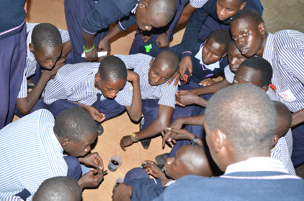 Students from Archbishop Orombi S.S making a homemade battery from soda.JPG