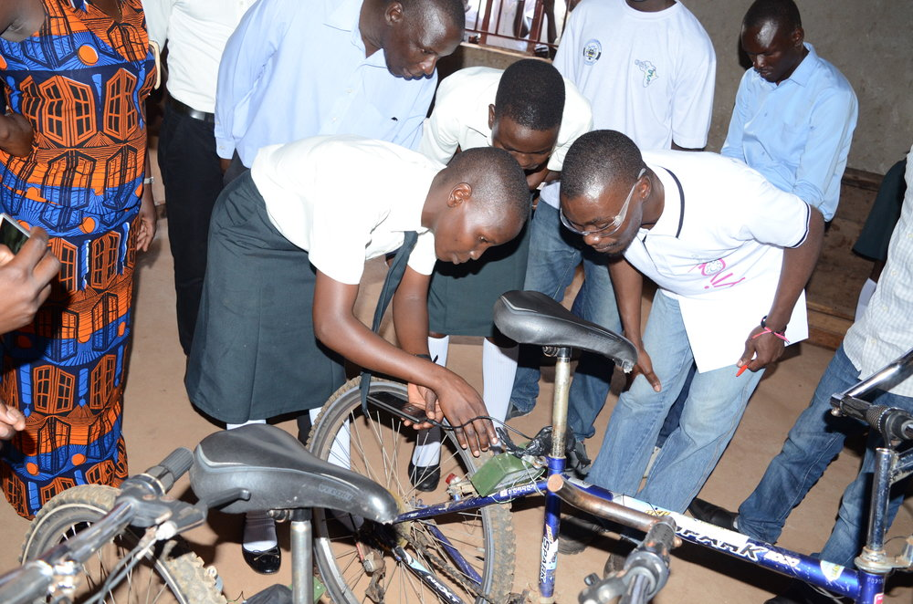 A student engineer from Leo Atubo College shows a judge how their bicycle powered charger works (1).JPG